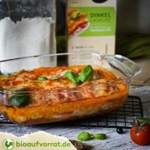 Auflaufform mit fertig gebackener Lasagne steht vor einer Packung Naturata Dinkel Lasagne. Die Lasagne ist mit frischem Basilikum dekoriert.