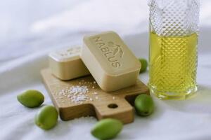 Seifen von Nablus Soap auf einem Brett. Angerichtet mit Olven und Olivenöl