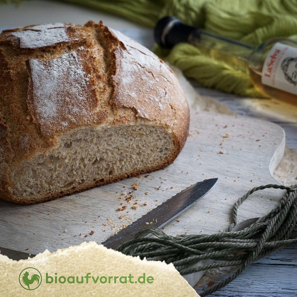 Ein angeschnittener Brotlaib liegt auf einem Holzbrett. Vor dem Brett liegt ein Brotmesser. Im Hintergrund ist eine Flasche weißer Balsamico-Essig zu sehen.