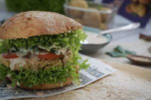Im Vordergrund ist ein Burger zu sehen, der mit grünem Lollobionda-Salat, saftigen Tomatenscheiben und einem knusprigen Falafel-Pattie gefüllt ist. Über dem Pattie verlläuft die Burgersoße. Im Hintergrund steht ein Schüsselchen mit Soße.
