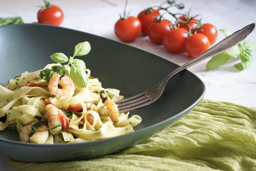 Zu sehen ist ein Teller, gefüllt mit Tagliatelle. Die Bandnudeln sind mit grünem Pesto, Spinat, Tomaten und Garnelen zubereitet. Hinter dem Teller liegt eine Kirschtomatenrispe.