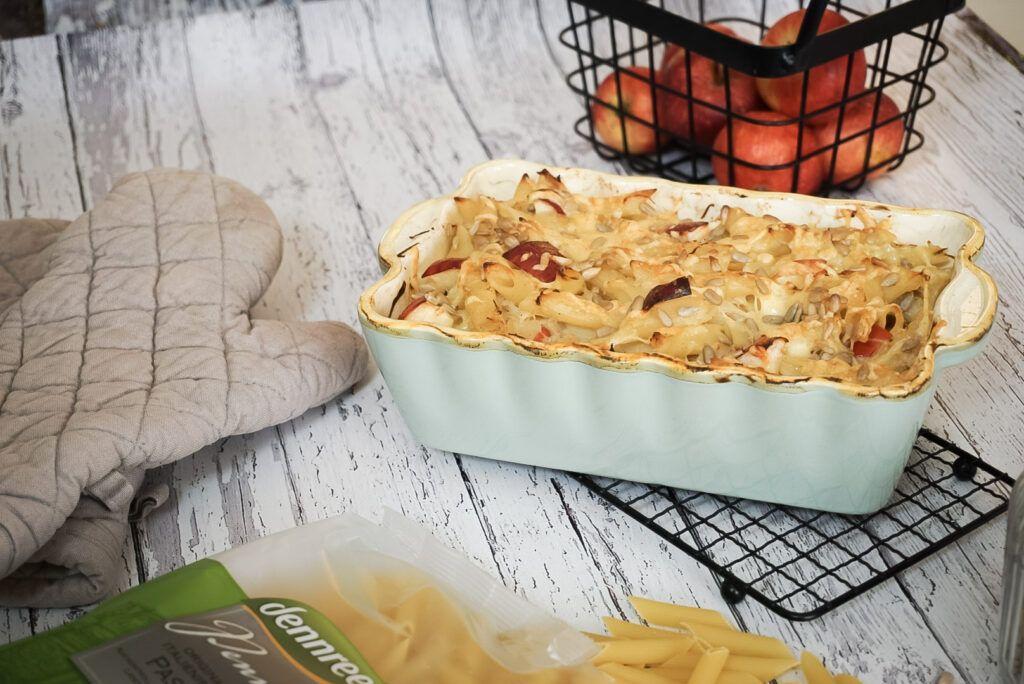 Auf einem weißen Holztisch steht eine Auflaufform. Neben der Auflaufform liegen Ofenhandschuhe und in der Form befindet sich ein fertig gebackener Nudelauflauf. Zu sehen sind Apfelstücke zwischen den Nudeln, gratinierter Käse und Sonnenblumenkerne auf dem Auflauf.