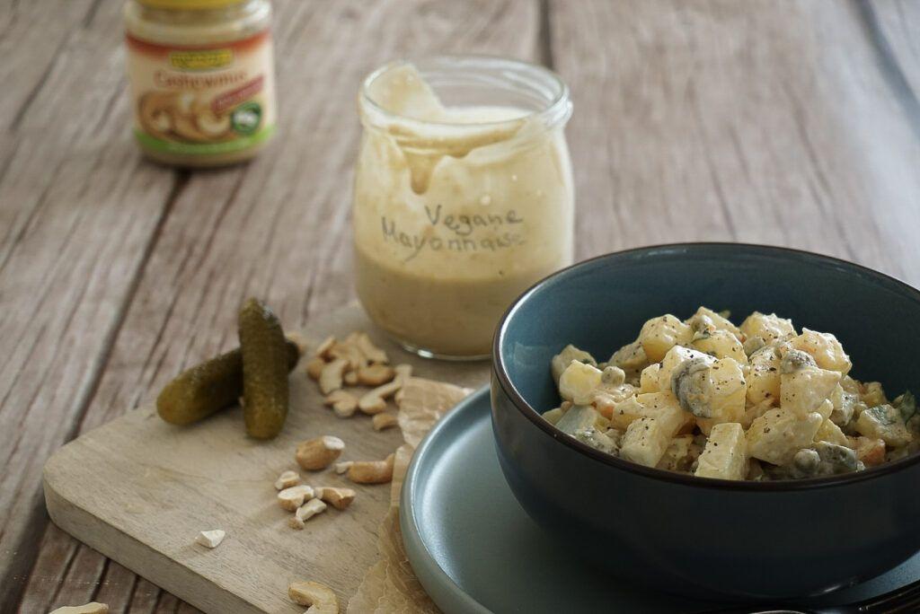 Eine Schüssel mit Kartoffelsalat steht auf einem Holzbrett. Neben der Schüssel steht ein Glas, in dem selbstgemachte, vegane Mayonnaise ist. Vor dem Glas liegen Gewürzgurken und Cashewkerne. Im Hintergrund befindet sich ein Schraubglas mit Rapunzel Cashewmus.